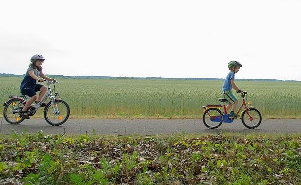 Radelnde Kinder entlang eines Feldes, Foto: J. Rocholl, Agentur FACE